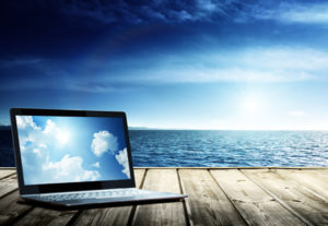 Clouds on Laptop on pier and atlantic ocean