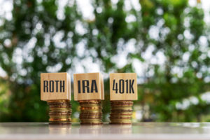 Wooden blocks with text IRA ROTH 401K. Business and finance concept.